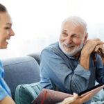 Homem branco de meia idade e mulher jovem conversando sobre as dicas para cuidador de idosos