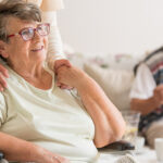 imagem de uma pessoa abraçando o idoso com mal de parkinson e outro idoso sorridente ao fundo