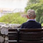 pessoa idosa sentada solitária em um banco na praça mostra como é a solidão do idoso